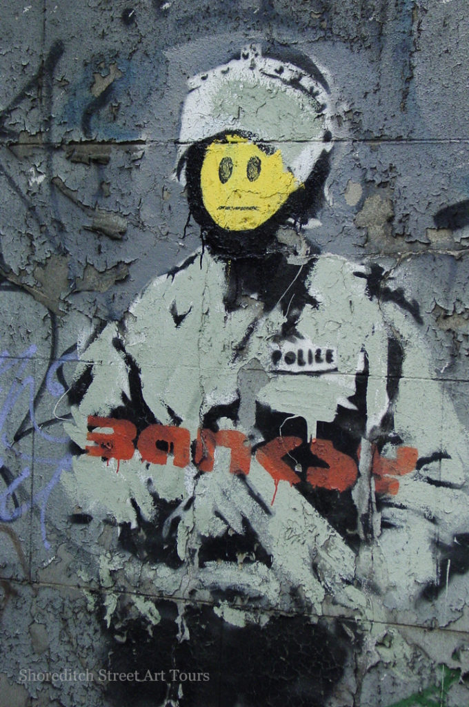Banksy stencil of a Smiley Copper in Shoreditch over Robbo, amended
