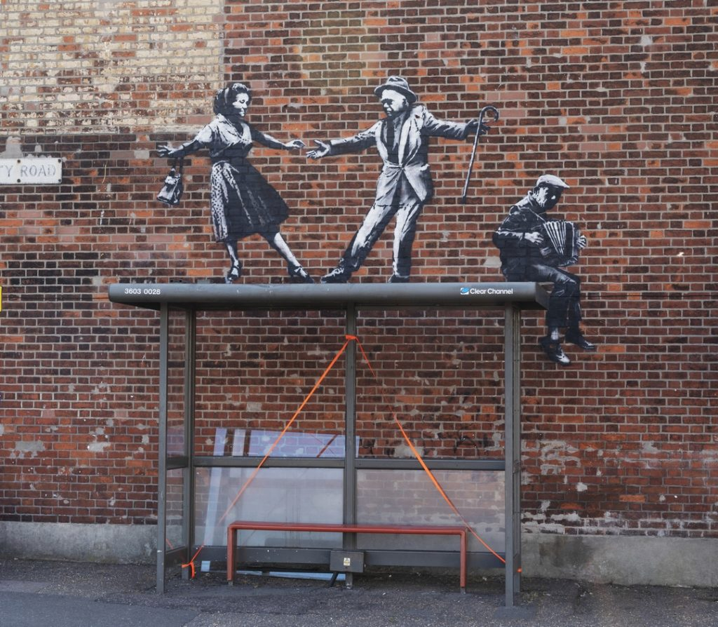 Banksy stencil of two dancers and an accordian player placed on top of a bus shelter in Great Yarmouth
