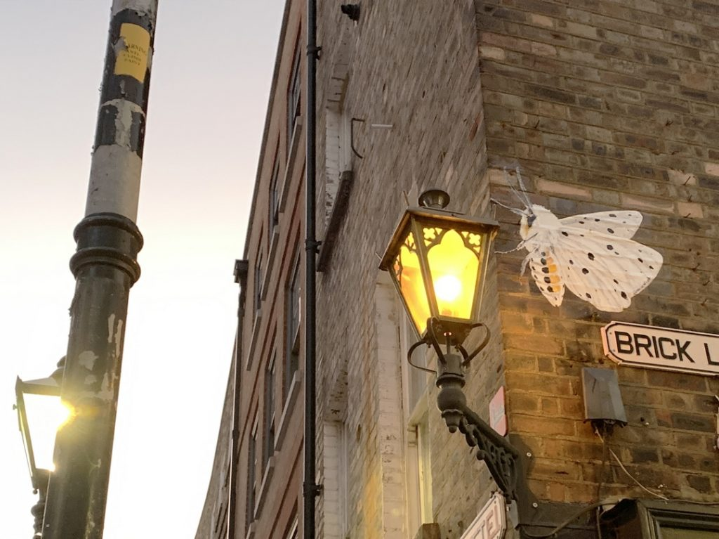 paste up street art of a moth perfectly positioned by a gas lamp in brick Lane Shoreditch by street artist Marie Alice