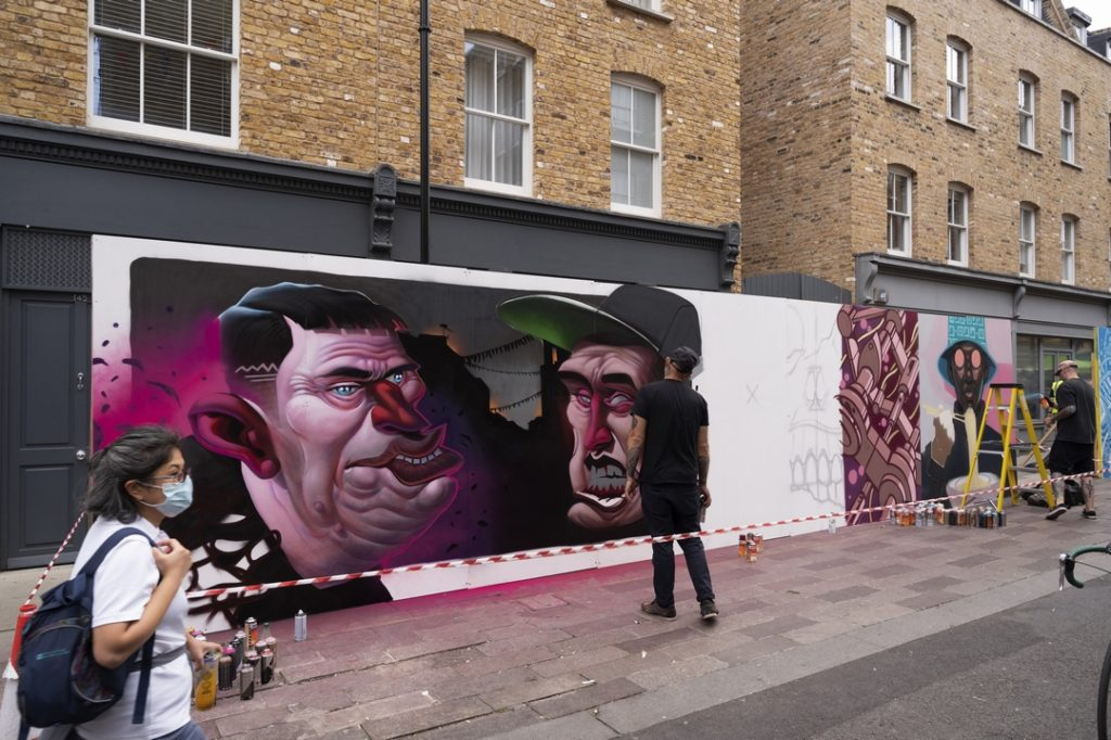 Street Artist Gent 48 painting on a board at the Whitecross Street Party