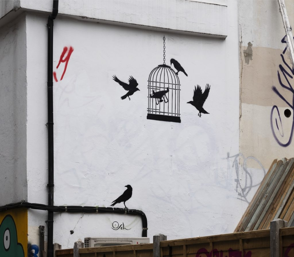 """Street art stencil onside of a building shoing a drone inside a birdcage with crows pecking outside the cage, by street artist Otto Schade, called """"Artificial Intelligence"""""""